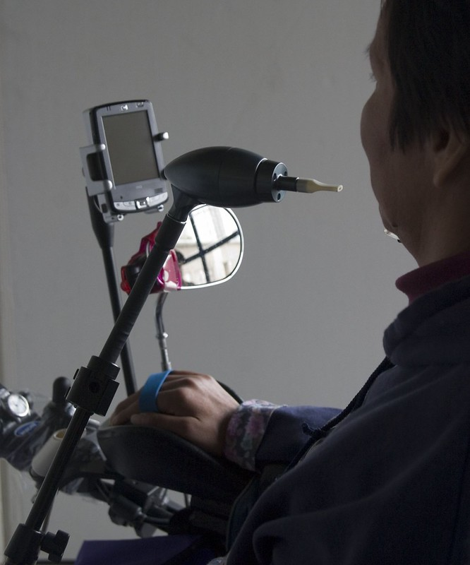 Quadripelegic controlling mobile phone connected to her wheel chair, using her Jouse
