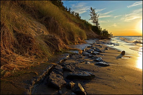 The setting sun reflects off of wet slabs of clay recently uncovered by the waves of Lake Michigan. This erosion took place within the last week and has exposed clay that looks a lot like rock. Photo by Tom Gill.