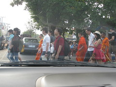 A mix of locals, monks and tourists cross the street