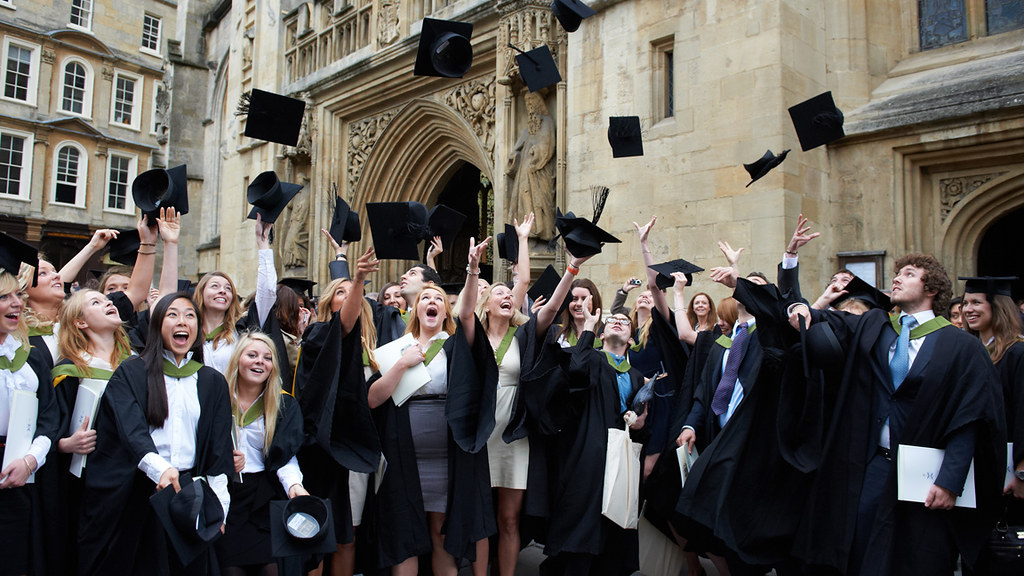 Graduates celebrating at their summer degree ceremony, throwing their hats in the air