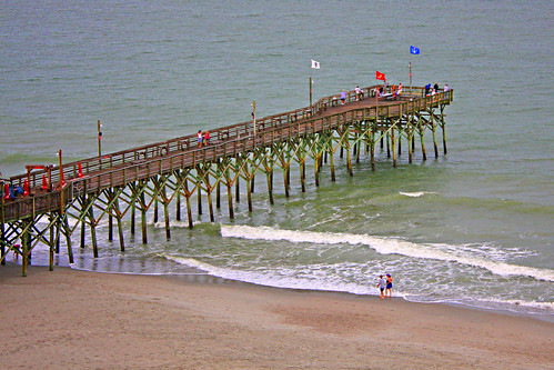 myrtlebeach southcarolina sc atlanticocean seashore seaside ocean saltwater beach barrierisland sand eastcoast coastline unitedstates us usa america pier pier14 pierfourteen fishingpier people fishermen flags pennants woodenpier boardwalk peoplelookingforseashells shells undertheboardwalk pilings pilingbraces surf waves backwash wavesbreaking breakingwaves