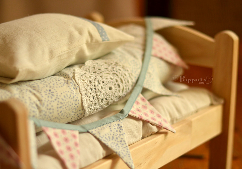Doll bedding in whites and blues with a matching bunting