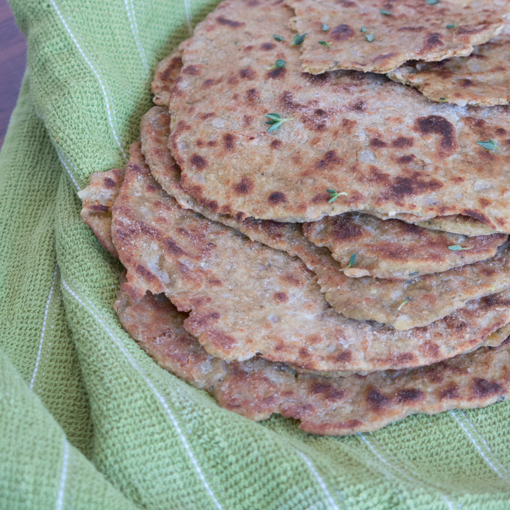 zucchini flatbreads stacked in a green towel with fresh thyme sprinkled on top