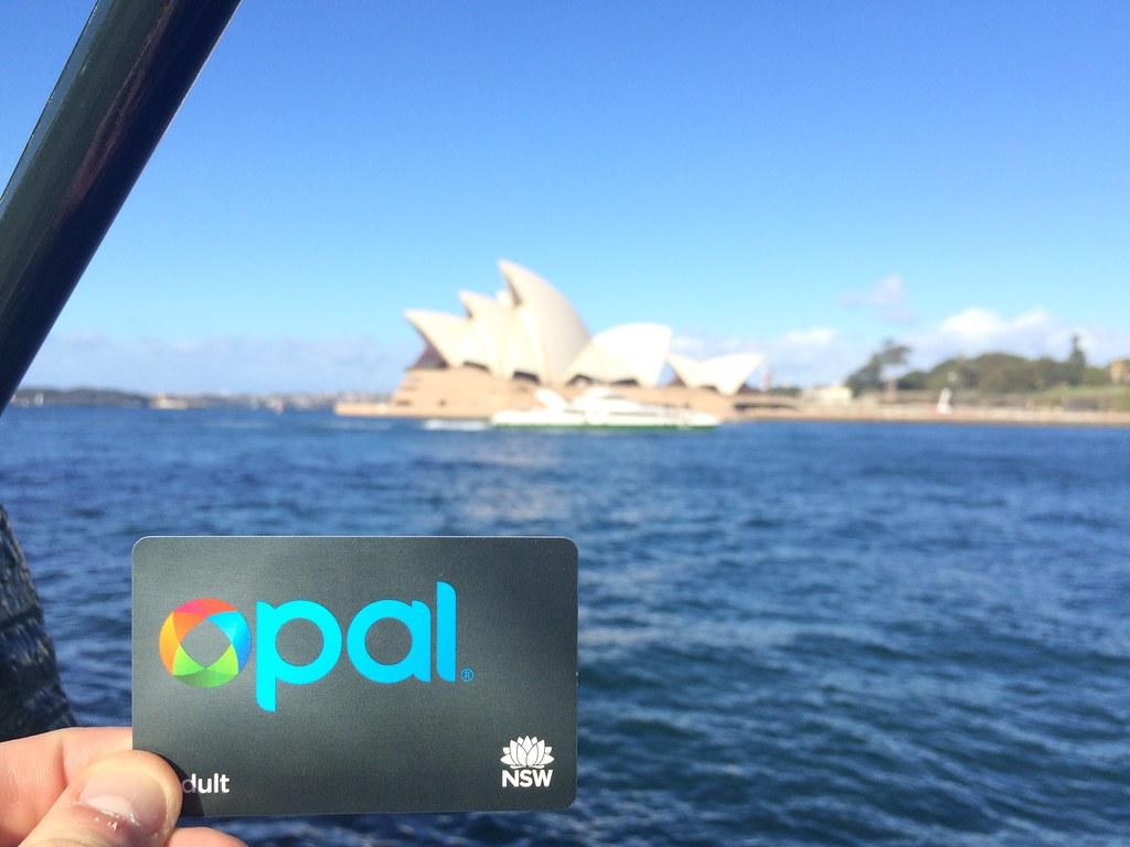 Adult Opal Card held infront of Sydney Opera House