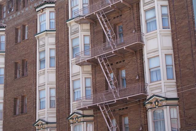 Façade en brique, bow window et escalier extérieur à SF