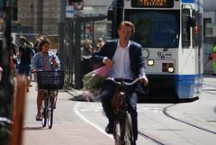 Student met een bosje bloemen op fiets