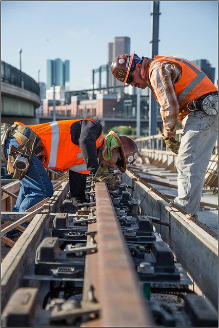 Photo of workers installing rail on South Platte River bridge
