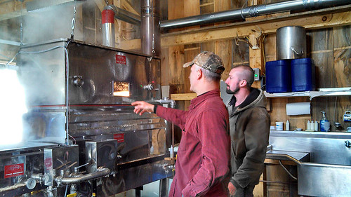 NRCS District Conservationist Ray Covino (right) talks with a maple sugar producer about how more efficient machinery helps both the producer and the environment. NRCS photograph.