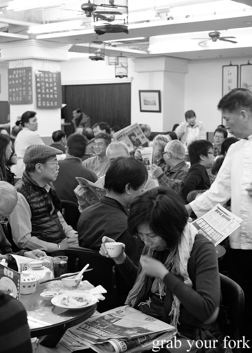 Yum cha crowd with newspapers at Lin Heung Tea House in Hong Kong