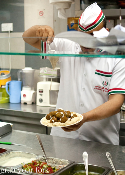 Adding tahini sauce to Jordanian falafel mahshi during a Frying Pan Adventures food tour in Dubai