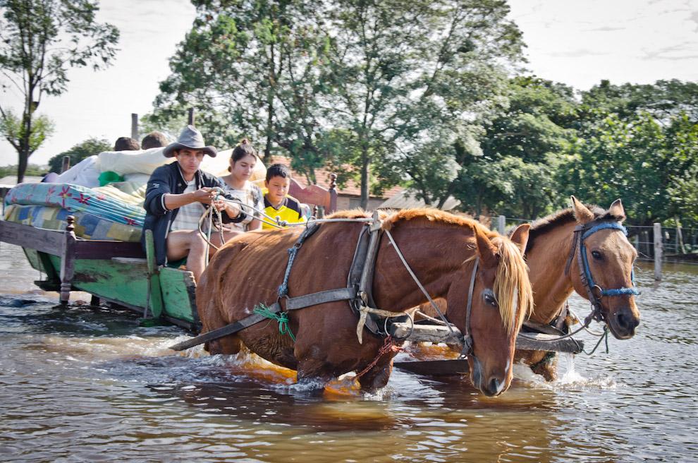 Una familia transita por las calles inundadas del Puerto La Niña, trasladando sus pertenencias a un lugar seco, al día siguiente de una rápida crecida del Río Jejuí, que los tomó de sorpresa. (Elton Núñez)