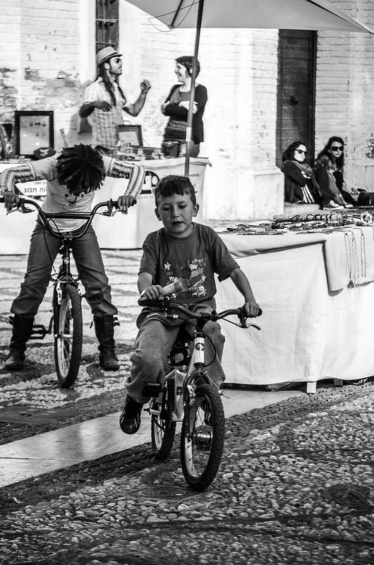 Kids ride bikes through vendors at Mirador San Nicolás in Granada's Albayzín.