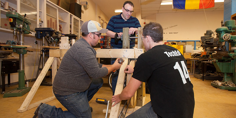 Teacher candidates Eric Foster, Chris Darnell and Scott Lewis (left to right) work on their pedal-powered lathe that they will display at the  Technological Education Expo on April 29.