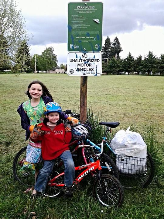 two kids on bikes cleaning up park on Earth day