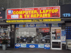"The same shopfront as above, but with a neater window display — the goods are now spaced out on shelves — and a new sign reading ""Broadway 4 / Computer, Laptop & TV Repairs"" above and ""We repair Apple products / No fix no charge"" below."