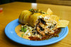 Fried Flour tortilla with a chipotle cream cheese, cilantro rice, black beans, grilled chicken and a salsa blend of tomatoes, onions, garlic and spices. Served on top of slaw, red pepper queso and orange-habanero marmalade. Topped candied jalapeno bits
