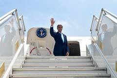 U.S. Secretary of State John Kerry - seen in triplicate due to his reflection - waves goodbye as he departs from New Delhi, following the Strategic Dialogue between the United States and India, as well as a meeting with Prime Minister Narendra Modi on August 1, 2014.