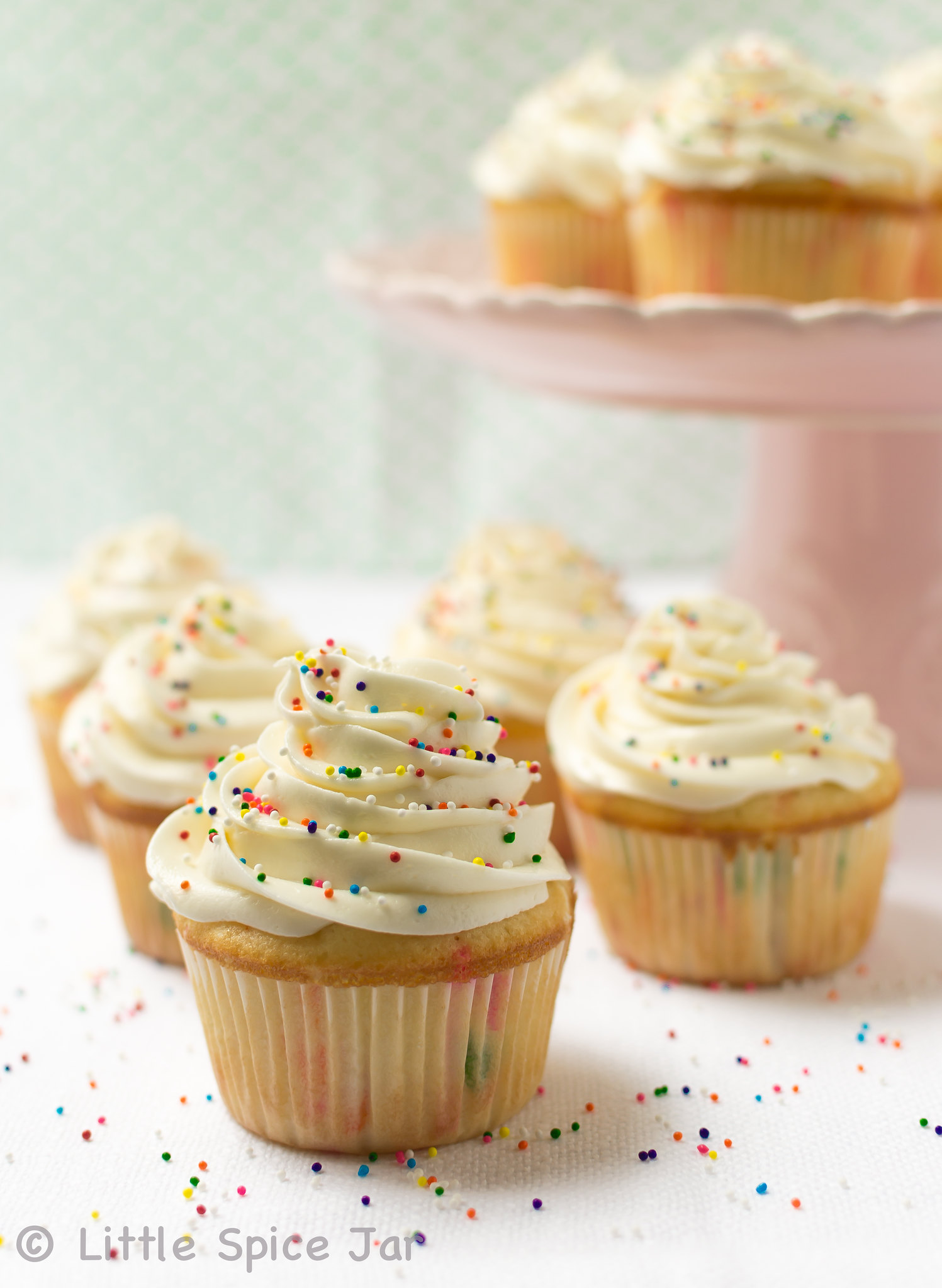 prepared funfetti cupcakes on white linen with cake stand holding more cupcakes in the back