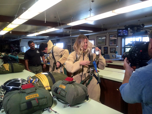 """Luis Gomez watches as Disney Channel's """"Movie Surfers"""" Golan Yosef and Taryn Brooks try their luck at suiting up in full smokejumper gear within two minutes of getting the call to mobilize. The exercise is part of a Disney Studios behind-the-scenes look at wildland firefighting. (U.S. Forest Service/Leo Kay)"""