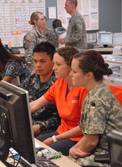 A Navy Nurse Corps Officer, an Auburn nursing student and an Army Nurse Corps Officer review an electronic medical record for one of the wounded at Walter Reed.