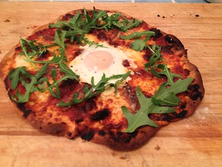 Homemade Pizza with Nduja, Felino Selame and anchovies topped with egg and rocket