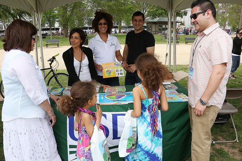 LULAC President Margaret Moran (in white) visits the USDA booth and discusses summer meals with an FNS employee. (photo by Luis Nuno Briones)