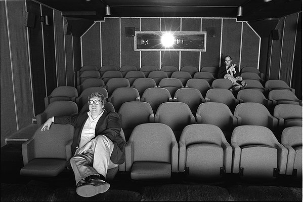 Roger Ebert sits closer to the front of the theatre, whereas Gene Siskel, without whom Roger would be nowhere near as famous, sits in his own favorite back seat.