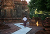 Burmese man in Longyi walking around giant Stupa, Bagan, Burma