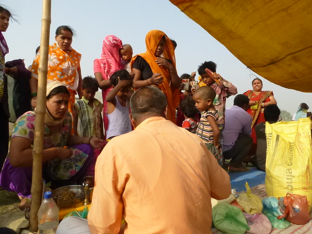 Pilgrims crowd around a seated priest with offerings of dal and rice.