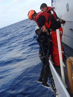 Crewmembers from the Coast Guard Cutter Key Largo rescue a Haitian migrant from the water west of Mona Island, Puerto Rico, Friday. The suspected smugglers, in an attempt to flee the area and avoid interdiction, allegedly threatened the migrants onboard and forced two Haitians, including a minor, overboard without life jackets. U.S. Coast Guard photo.