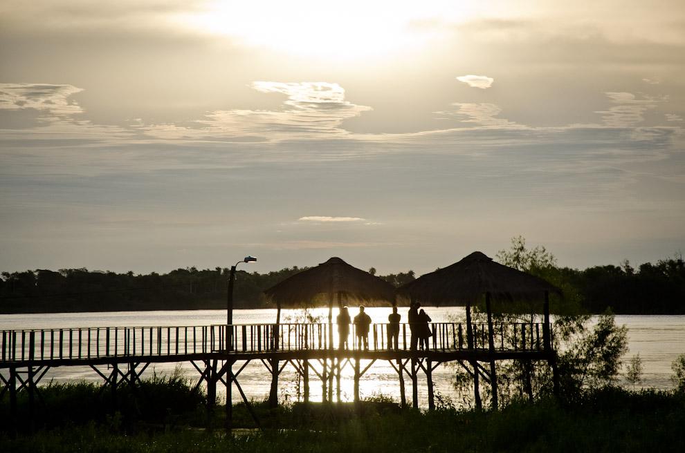 Turistas observan el atardecer en el muelle sobre el Río Paraguay, un lugar donde antes era el Puerto de Humaitá, un puerto que en épocas anteriores  llegó a ser la fuerza económica del Paraguay por su estratégica ubicación geográfica. (Elton Núñez)