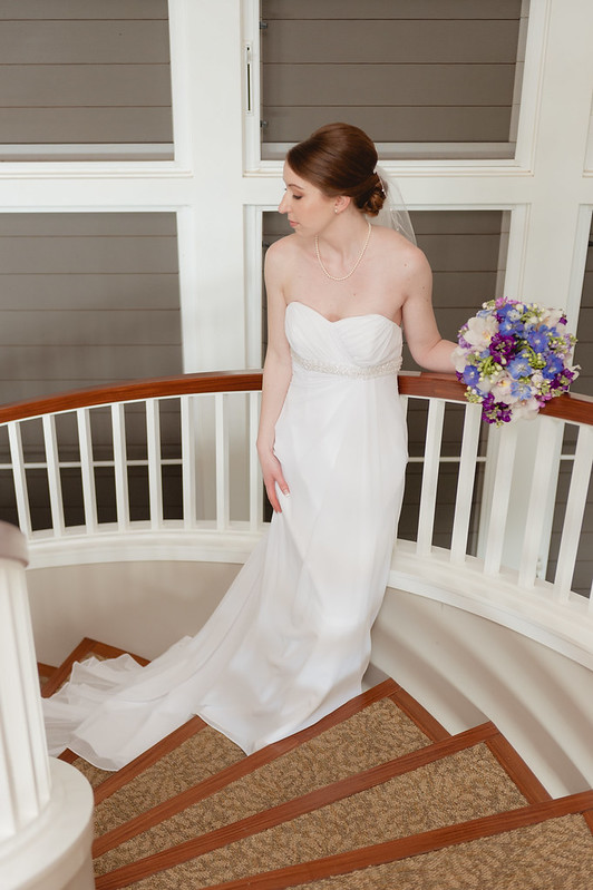 A maui bride poses on the staircase at the sugar beach events building.