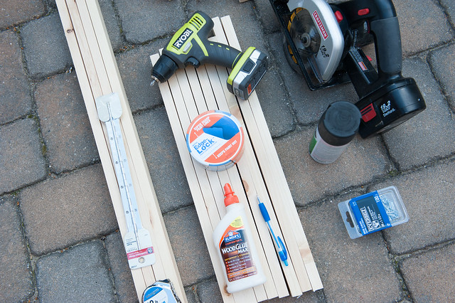 Supplies to make wood rack including wood pieces, piano hinge, drill, saw, nails, wood glue, painters tape and chalkboard spray paint