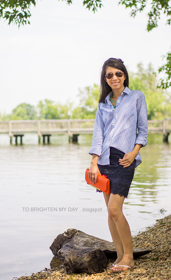 turquoise necklace, blue striped shirt, navy lace skirt, orange clutch