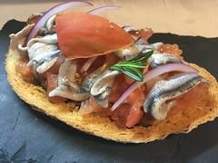 Tostas de pan payes con tomate escaldado, boquerones y sal maldón