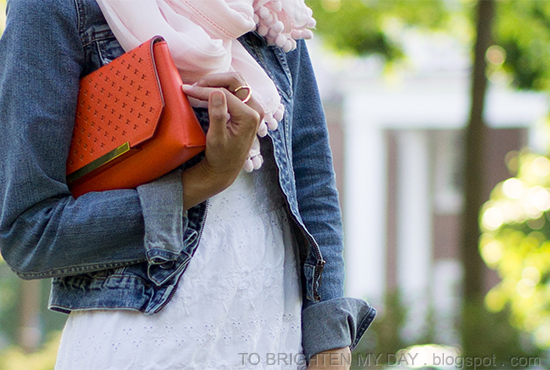 light pink scarf, white eyelet dress, orange clutch