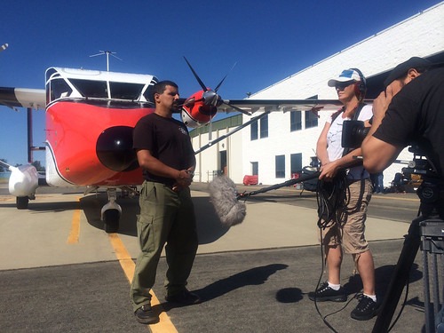 "A Disney Studios crew films U.S. Forest Service smokejumper Luis Gomez as he explains the intricacies of his work. The footage will be seen during a Disney Channel special and as part of the extras when the animated film ""Planes: Fire and Rescue"" is released on DVD. The Sherpa aircraft behind Gomez is used to fly smokejumpers to locations and is the lead ""character"" in the film. (U.S. Forest Service/Leo Kay)"