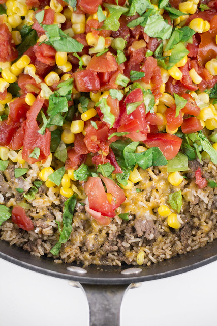 Easy to make One Pan Taco Casserole recipe! Ingredients include lettuces, tomatoes, corn, instant rice and shredded cheese.