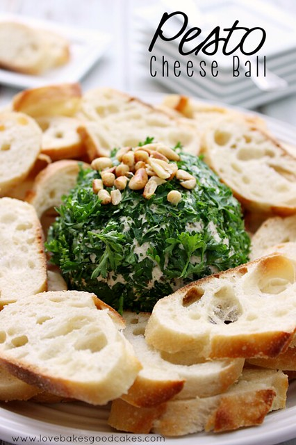 Pesto Cheese Ball with bread slices on a plate.