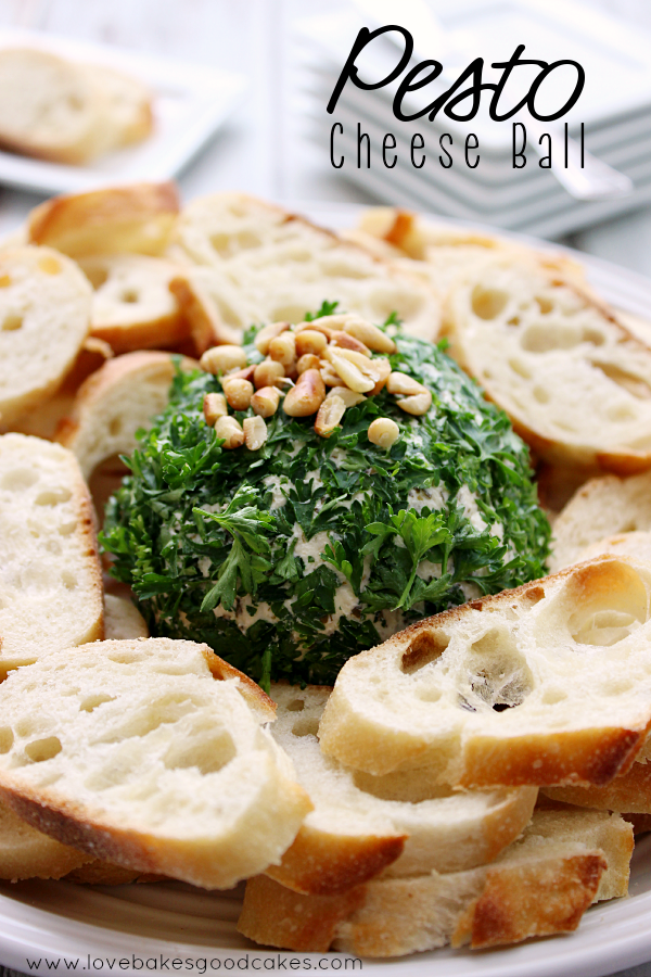 Pesto Cheese Ball with bread slices on a serving plate.