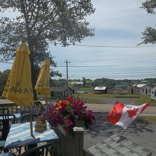 Flowers and flag, deck of Rick's Fish and Chips, St. Peter's #princeedwardisland #pei #stpeters #ricksfishandchips  #flowers #flag #canada