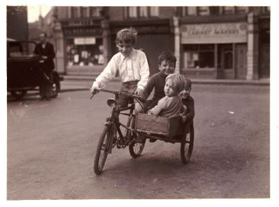 Children riding a bicycle and sidecar, about 1930 - 1