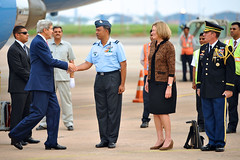 U.S. Secretary of State John Kerry is greeted by Indian Air Force Commodore C.K. Kumar as he arrives at Palam Air Force Base in New Delhi, India, on July 30, 2014, for a Strategic Dialogue with Commerce Secretary Penny Pritzer. [State Department photo/ Public Domain]