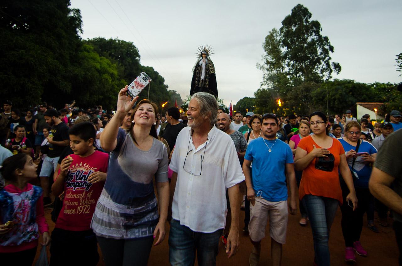 El creador del espectáculo artístico y religioso de Tañarandy, el señor Koki Ruíz, encabeza la procesión de la Virgen Dolorosa mientras una admiradora se toma un selfie con él. (Elton Núñez).
