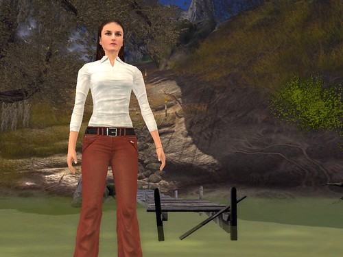 Image Description: Eve standing in front of a river; there is a pier on the other side.