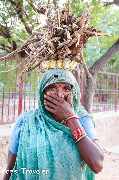 woman blushing with hand on face bangles in hand wood on head