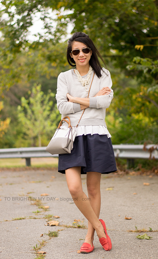 wrapped pearl necklace, ruffled sweatshirt, navy skirt, crossbody colorblocked bag, red loafers