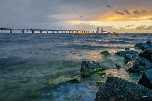 bridge sunset sea sky orange seaweed green water yellow waves slow purple cloudy sweden stones foam shutter malmö öresundsbron theøresundbridge skanecounty