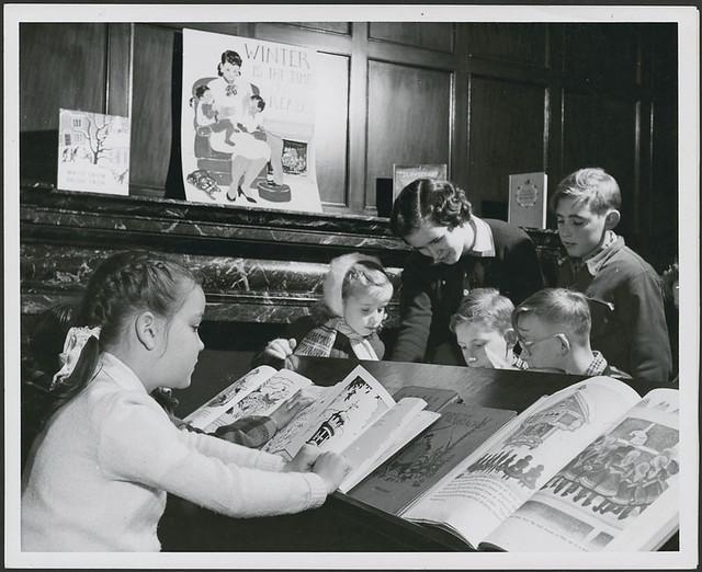 Miss Joan Heatley, librarian, helping a group of children, Willistead Park public library branch... / Mme Joan Heatley, bibliothécaire à la succursale de la Bibliothèque de Willistead Park, aide un enfant à choisir un livre...