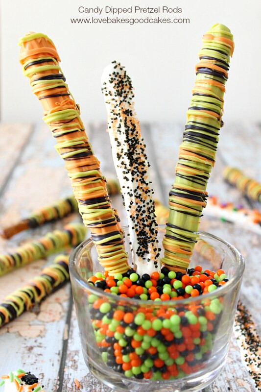 Candy Dipped Pretzel Rods standing up in a glass of multi-colored candy.